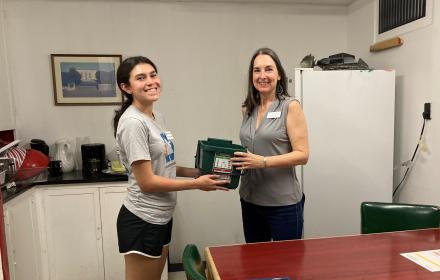A Resource Recovery student intern hands a composting bin to a UT staff member.