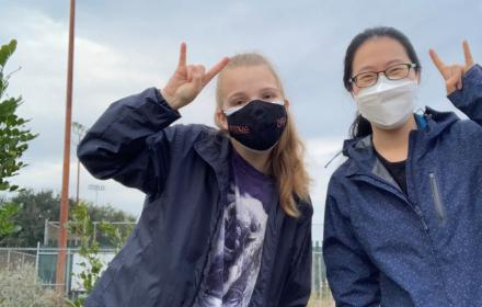 Two smiling students wearing masks hold up a Hook 'Em at the UT Microfarm.